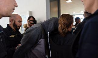 Der Angeklagte wird von mehreren Polizisten zum Gerichtssaal geführt. (Foto)