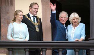 Der britische Thronfolger Prinz Charles und seine Ehefrau Camilla stehen mit Burkhard Jung, Bürgermeister von Leipzig und dessen Frau Ayleena auf dem Balkon des Rathauses und winken. (Foto)