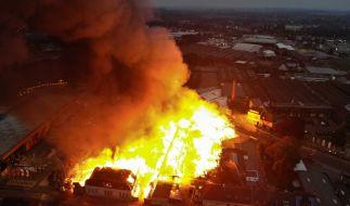 Helle Flammen schlagen aus einem Gebäudekomplex in Mönchengladbach im Stadtteil Eicken (Luftaufnahme mit Drohne). Das Feuer war in dem Areal ausgebrochen, in dem neben einer Schreinerei auch noch weitere Betriebe untergebracht sind. (Foto)