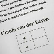 Ein Mann hält vor der Wahl einen Stimmzettel im Plenarsaal im Europaparlament.