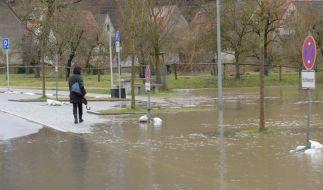 Eine Frau geht an einem überfluteten Parkplatz vorbei. (Foto)