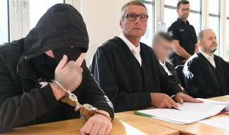 Der 19-jähriger Angeklagte (l) zeigt im Gerichtssaal im Landgericht den Mittelfinger. (Foto)