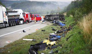 Trümmerteile liegen an der Seite der Autobahn 9 an der Unfallstelle, im Hintergrund liegt ein Fahrzeug auf der Seite. (Foto)