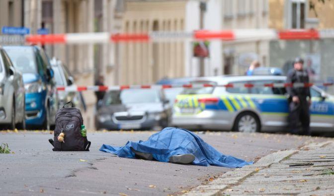 Eine abgedeckte Leiche liegt in einer Straße. Bei den Schüssen vor einer Synagoge in Halle sind nach ersten Erkenntnissen zwei Menschen getötet worden.