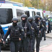 Polizisten mit Schutzhelmen machen sich auf die Suche nach dem Täter.