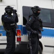 Polizisten stehen in Halle/Saale. Bei Schüssen sind nach ersten Erkenntnissen zwei Menschen getötet worden.