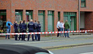 Polizisten und Passanten stehen vor einem Haus in der Innenstadt von Neuss. Nach Schüssen ist eine 27-jährige Frau gestorben. (Foto)