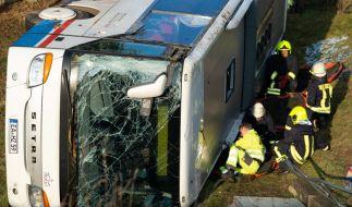 Einsatzkräfte installieren zum Aufrichten des verunglückten Schulbusses Hebekissen. (Foto)