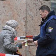 Ein Polizist hilft einer älteren Frau in der Nähe eines Tatortes am Heumarkt eine Kerze anzuzünden.