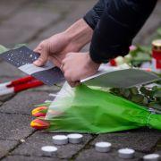 Eine Frau legt als Zeichen der Trauer eine Karte und Blumen an einem Tatort in Kesselstadt nieder.