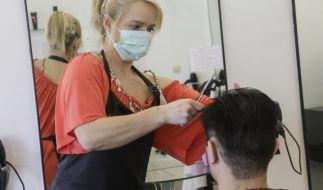 Wenn Friseure ihre Salons wieder öffnen, müssen sie und ihre Kunden einen Mundschutz tragen. (Foto)