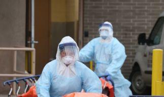 New Yorker Krankenhausmitarbeiter in Schutzkleidung schieben Tragen mit kürzlich Verstorbenen Opfern der Covid-19-Erkrankung aus dem Krankenhaus. (Foto)
