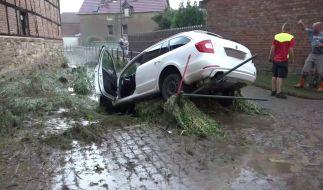Ein Auto, das von den Wassermassen mitgerissen wurde, hängt in einem Bachbett in Beckendorf nahe Oschersleben nach einem heftigen Unwetter mit Starkregen und Hagel. (Foto)