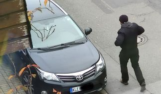 Das Fahndungsbild der Polizei Krefeld zeigt einen Tatverdächtigen, der an einem Einbruch in die Nebenstelle Emmerich des Hauptzollamtes Duisburg beteiligt gewesen sein soll und zu einem Fahrzeug geht, dessen Kennzeichen gefälscht wurden. (Foto)