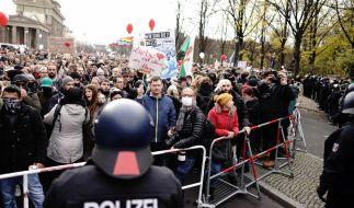 Teilnehmer einer Demonstration gegen die Corona-Einschränkungen der Bundesregierung stehen nach dem Brandenburger Tor an einer Absperrung Polizisten gegenüber. (Foto)