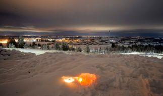 Eine Kerze brennt im Schnee für die Opfer eines Erdrutsches. Drei Tage nach dem Erdrutsch haben die Rettungskräfte eine zweite Leiche im Unglücksgebiet gefunden. (Foto)