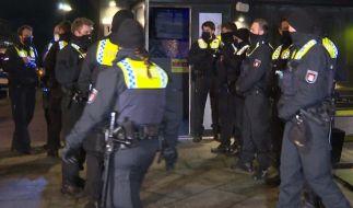 Polizisten stehen vor einer Shisha-Bar. Eine Shisha-Bar in Hamburg hatte trotz der geltenden Corona-Auflagen geöffnet. (Foto)