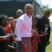 Barack Obama, ehemaliger Präsident der USA, seine Halbschwester Auma Obama (l) und ihre Großmutter Sarah Obama (2.v.r) gehen durch Kogelo, Kenia (2018).