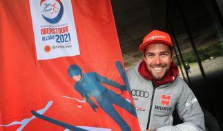 Johannes Rydzek, deutscher Nordischer Kombinierer, steht neben der offiziellen Fahne der Nordischen Ski-WM 2021. (Foto)