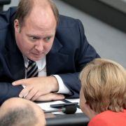 Helge Braun und Angela Merkel unterhalten sich bei der Generaldebatte im Deutschen Bundestag (2018).