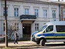 Mitarbeiter der Polizei und ein Fahrzeug der Kriminalpolizei stehen in der Bahnhofsstraße. Mit einer Armbrust soll sich ein Mann dort selbst verletzt und zuvor eine Frau angegriffen und am Kopf verletzt haben. (Foto)
