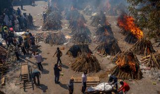 Mehrere Scheiterhaufen mit Leichnamen der Opfern vom Covid-19 brennen auf einem Gelände. (Foto)