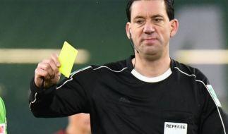 Schiedsrichter Manuel Gräfe zeigt dem Wolfsburger Tisserand die Gelbe Karte. (Foto)