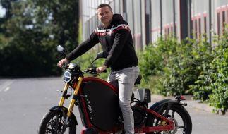 Influencer Aaron Troschke stützt sich auf ein Elektromotorrad. (Foto)