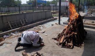 Ein Mann verneigt sich aus Respekt, während ein Corona-Opfer, für das sich keine Angehörigen gemeldet haben, in einem Krematorium verbrannt wird. (Foto)