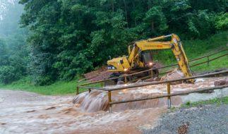 Mit schwerem Gerät arbeiten Helfer an einer überfluteten Straße nach heftigen Unwettern in Altensteig. (Foto)