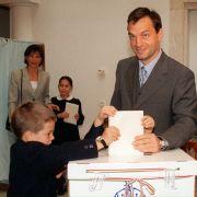 Viktor Orban steht gemeinsam mit seinen Kindern Gaspar (l.), Sara (M., verdeckt von Wahlzettel), Rahel (Hintergrund, r.) und seiner Frau Aniko Levai in einem Wahllokal 1998.