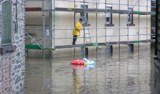 Ein Mann steht auf einem Gerüst und betrachtet die überflutete Straße vor dem Haus. (Foto)