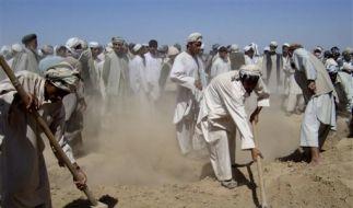 Afghanische Dorfbewohner begraben die Toten nach dem Luftangriff (Foto)