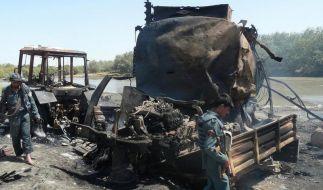 Afghanische Sicherheitskräfte inspizieren einen der ausgebrannten Tanklastzüge. (Foto)