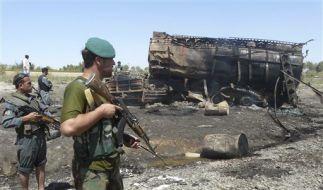 Afghanische Sicherheitsmitarbeiter bewachen einen der ausgebrannten Tanklastzüge in Kundus. (Foto)