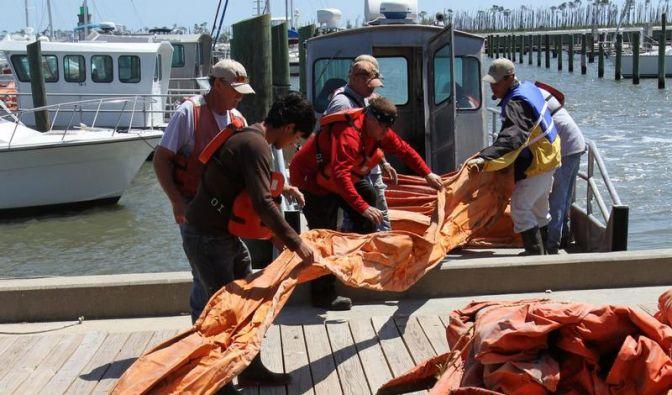 Arbeiter im Golf von Mexiko beladen ein Boot mit einer Ölsperre. (Foto)