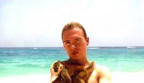 Auf dem Twitter-Profilfoto posiert Luka Magnotta, mutmaßlicher Porno-Killer aus Kanada, am Strand mit einem Äffchen als Halskette. (Foto)