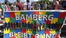 Teilnehmer einer Kundgebung protestieren am Freitag (04.06.10) in Bamberg (Bayern) mit einem Schild, auf dem 'Bamberg bleibt bunt' steht, gegen den dort stattfindenden NPD-Parteitag. Mit einer Menschenkette und einem multikulturellen Fest demonstriert Bamberg gegen den am Wochenende (05./06.06.10) stattfindenden Bundesparteitag der NPD in der Stadt. Bamberg hatte vergeblich auf dem Rechtsweg versucht, den zweiten Parteitag der Rechtsextremen nach 2008 zu verhindern. (zu ddp-Text) Foto: Timm Schamberger /ddp Foto: ddp