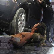 Danijel Peric singt O sole mio während 15 Autos über seinen Bauch fahren.