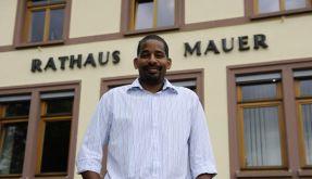 Bürgermeister John Ehret steht vor dem Rathaus in Mauer. Baden-Württembergs erster dunkelhäutiger Bürgermeister hat dort sein Amt angetreten. (Foto)