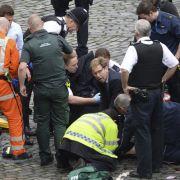Der Parlamentsabgeordnete Tobias Ellwood (M) der Conservative Party kümmert sich in der Nähe des britischen Parlaments in London um verletzte Personen.