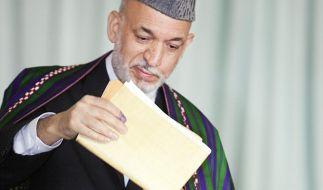 Der afghanische Präsident Hamid Karsai wirft bei der Wahl am 28. August 2009 seinen Wahlzettel in ei (Foto)