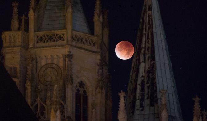 Der rötlich gefärbte Mond leuchtet am 28.09.2015 in Erfurt (Thüringen) hinter dem Dom. (Foto)