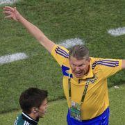 Der vierte Schiedsrichter muss es ausbaden: Ukraines Coach Oleg Blochin breitet zornig seine Schwingen aus.