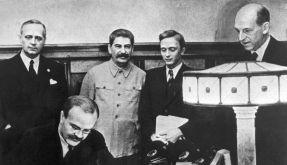 Die Außenminister Wjatscheslaw Molotow (vorn) und Joachim von Ribbentrop (l.) unterzeichnen den Pakt (Foto)