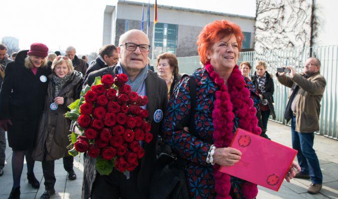Die Initiatoren Regina Ziegler (r.) und Volker Schlöndorff (l.) übergeben am 08.03.2016 am Bundeskanzleramt in Berlin einen Brief und einen Blumenstrauß für Bundeskanzlerin Angela Merkel (CDU). (Foto)