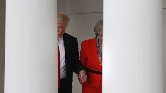 Donald Trump (links) und Großbritanniens Premierministerin Theresa May gehen Hand in Hand am 27. Januar den Säulengang am Weißen Haus in Washington entlang.