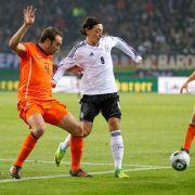 Duell der Ausrüster: Mesut Özil (rechts, in Adidas-Trikot und Nike-Schuhen) gegen Joris Mathijsen (Adidas-Schuhe und Nike-Trikot).