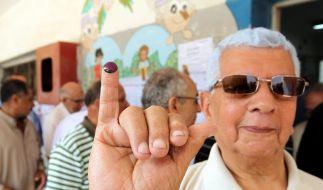 Ein Ägypter zeigt seinen mit Tinte markierten Finger zum Beweis, dass er gewählt hat. (Foto)