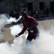 Ein ägyptischer Demonstrant wirft einen Tränengaskanister.